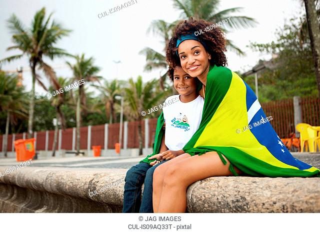 Young mother and son wrapped in Brazilian flag on Ipanema beach, Rio De Janeiro, Brazil