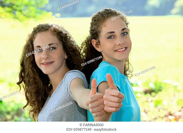 Smiling beautiful young teenage sisters giving a thumbs up of approval as they enjoy a day outdoors in the sunshine during their summer vacation