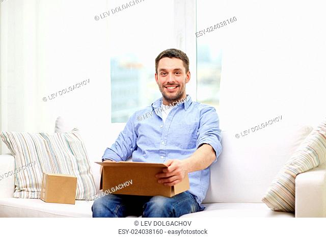 delivery, mail and people concept - happy man with cardboard boxes or parcels at home