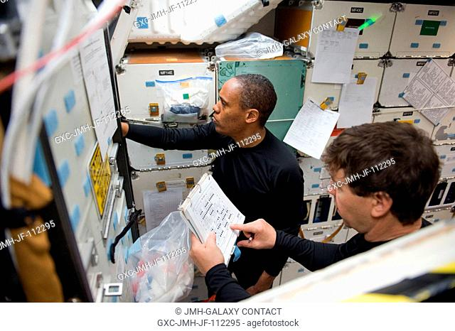 NASA astronauts Michael Barratt (foreground) and Alvin Drew, both STS-133 mission specialists, participate in a post insertionde-orbit training session on the...