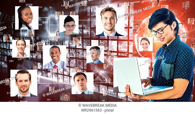 Business person using laptop against portraits