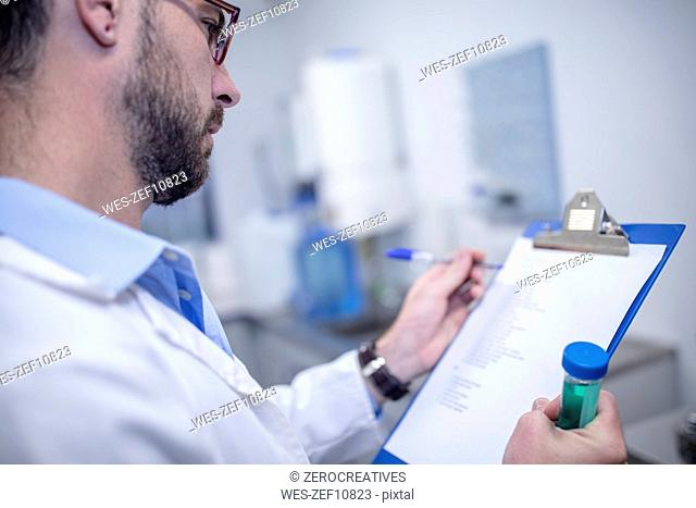 Scientist with clipboard and test tube working in laboratory