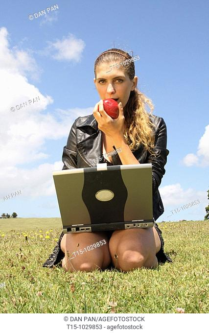 girl eating an apple using a laptop in a park