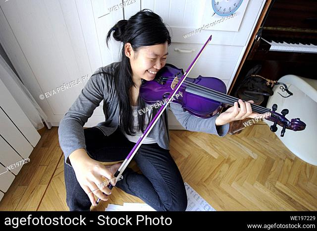 young asian girl playing the violin in her bedroom in Madrid (Spain)