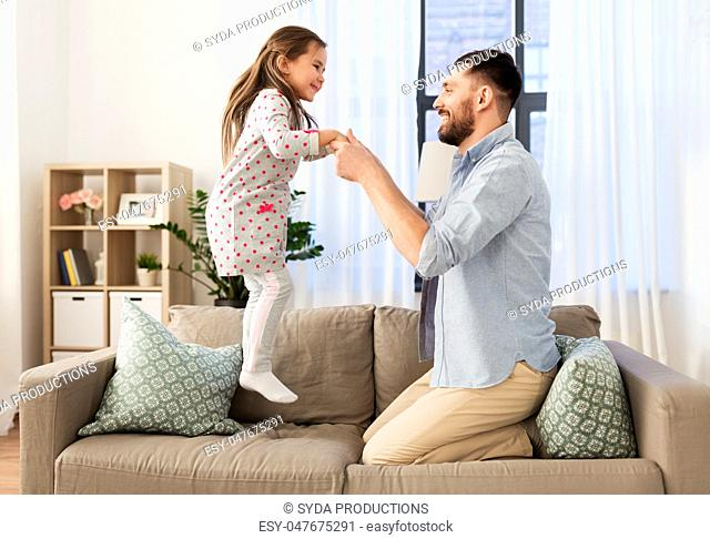 father and daughter jumping and having fun at home