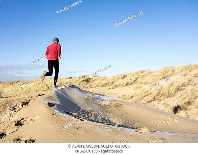 Man jogging on frost coverd dunes on Seaton Carew beach, north east England, United Kingdom