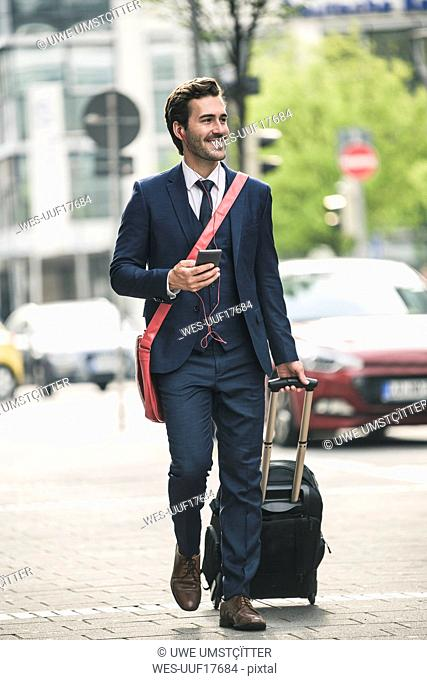 Smiling businessman walking in the city with cell phone and suitcase