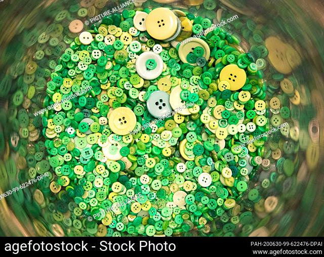 """30 June 2020, Hamburg: Green Buttons are lying in a plastic column at a press conference on the textile seal """"""""Green Button"""""""" with Federal Development Minister..."""