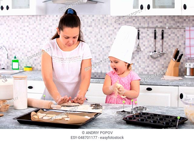 Girl Wearing Chef Hat Helping Her Mother To Make Cookies At Kitchen