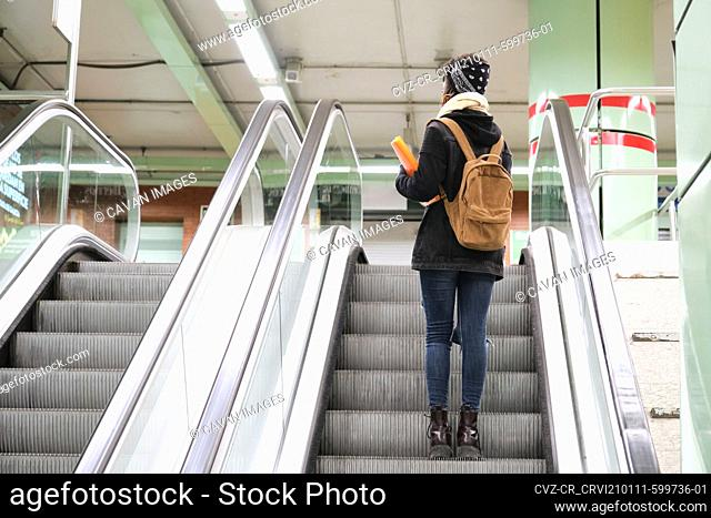 University female african student wearing protective face mask taking escalator upstairs at the underground station. New normal in public transport