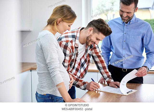 Couple with real estate agent signing contract in kitchen of new apartment