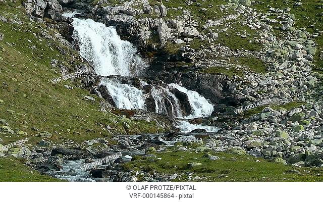 Small water fall in a spring landscape at the Julier Pass near St.Moritz, Switzerland