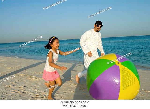 Girl playing beach ball with father on beach, side view