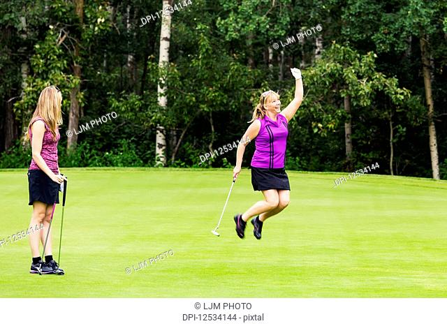 A mature woman golfer jumping for joy for sinking a putt while her teammate looks on; Edmonton, Alberta, Canada