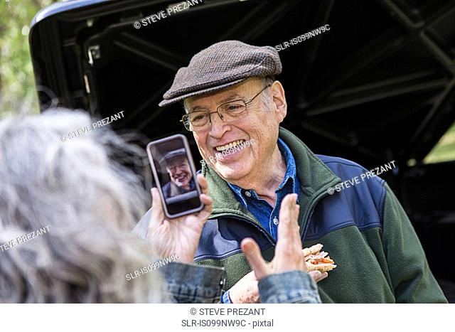 Senior woman taking picture message of smiling man outdoors