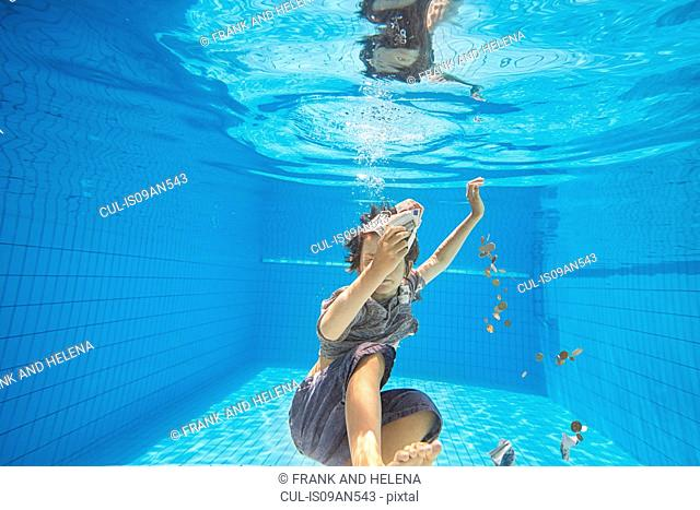 Underwater view of boy in swimming pool grabbing euro notes and coins