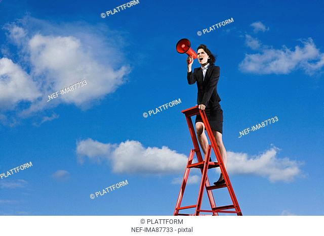 Businesswoman standing on top of red ladder against blue sky and shouting through red megaphone