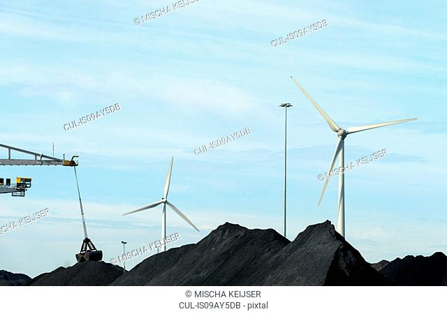 Wind turbines in between piles of coal in harbour, Flushing, Netherlands