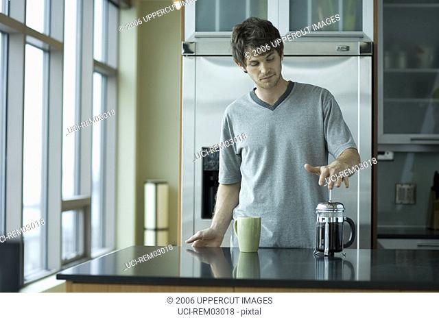 Young man drinking coffee in kitchen