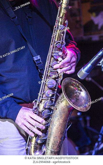 Saxophone Player hands, Saxophonist playing jazz music. Alto sax musical instrument closeup. Musician in blue shirt with saxophone and microphone close up