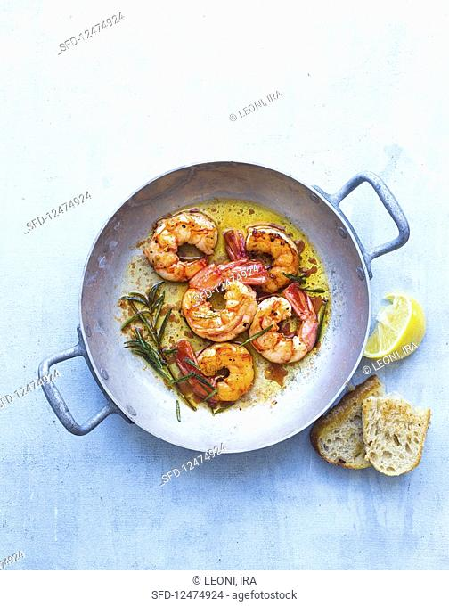 Fried prawns with rosemary in a pan
