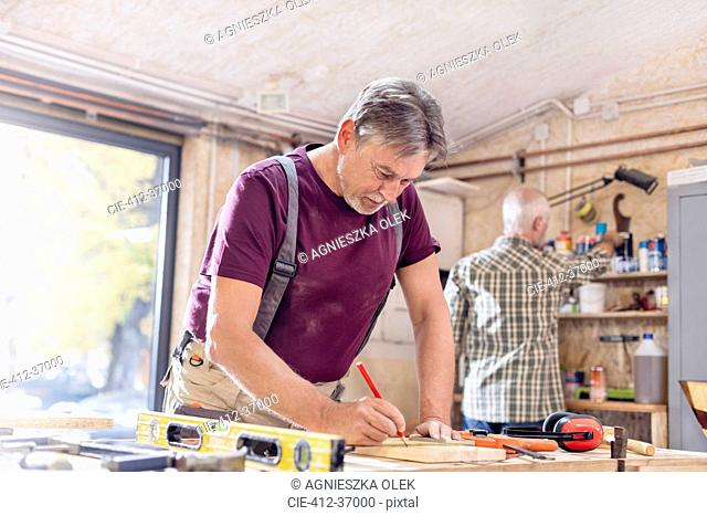 Male carpenter measuring and marking wood plank on workbench in workshop