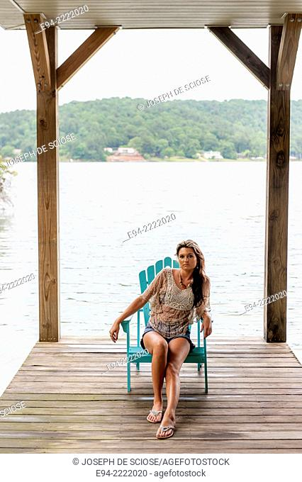 A 27 year old brunette woman sitting on an Adirondack chair on a dock by a lake