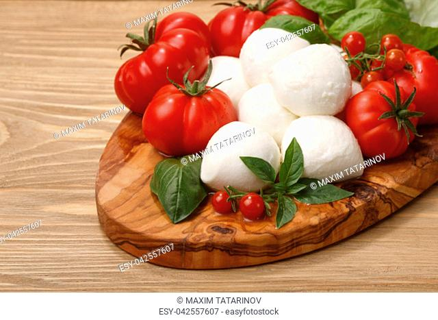Italian cuisine. Mozzarella, heirloom tomatoes, basil leaves on a wooden serving plate. Selective focus on cheese