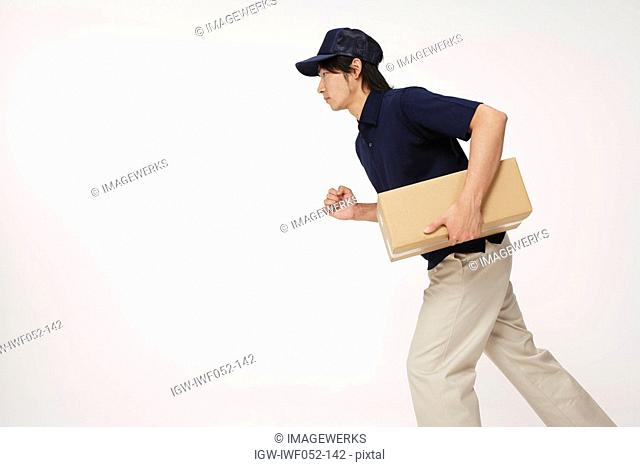 Delivery man carrying cardboard box, side view