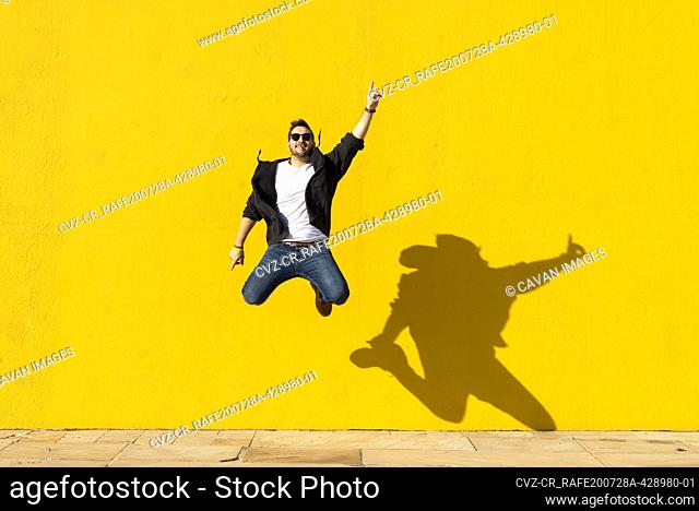 Young man with sunglasses jumping in front of a yellow wall