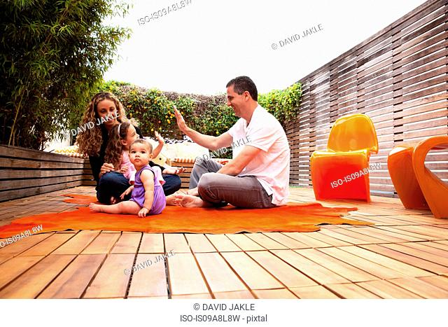 Family sitting on rug on patio