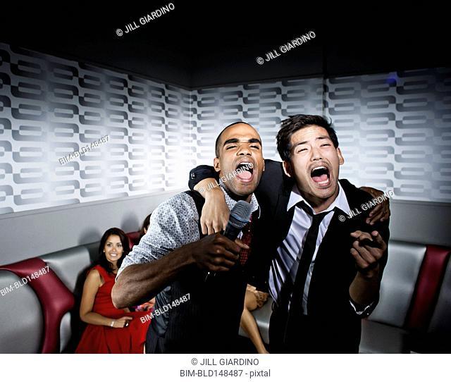 Friends singing karaoke in nightclub