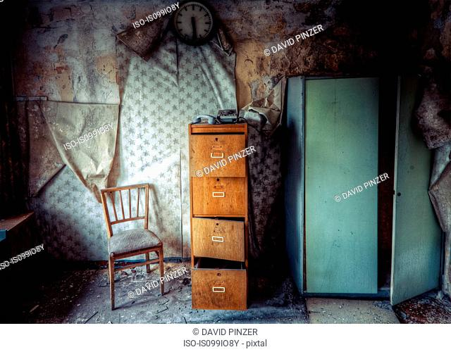 Abandoned building with chair and filing cabinet