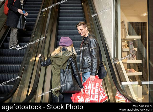 Young couple carrying shopping bags while standing on escalator in shopping mall