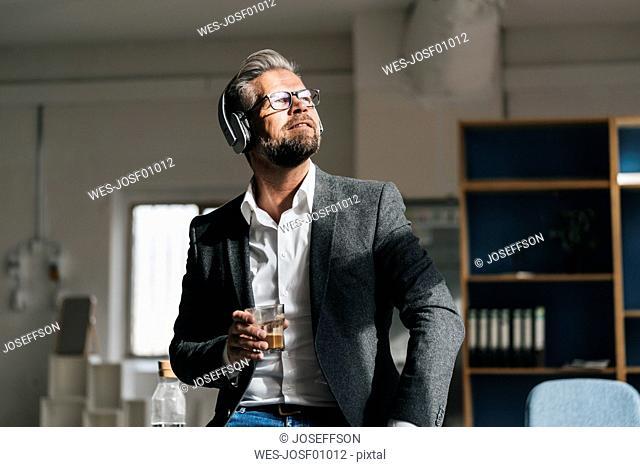Businessman wearing head phones , listening music