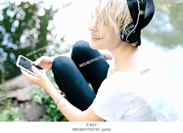 Young woman sitting at lakeside in park wearing headphones and holding cell phone