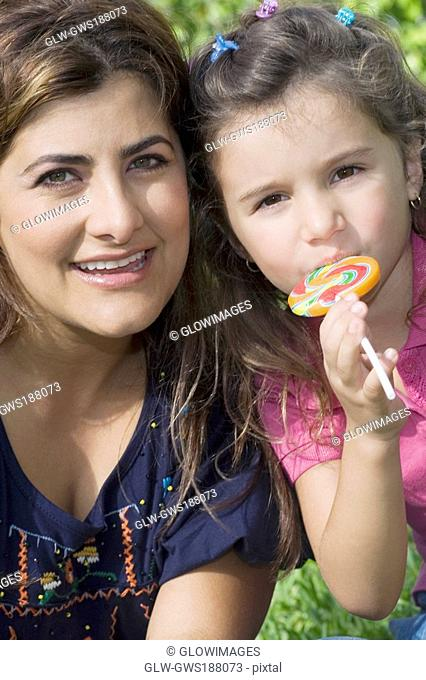 Portrait of a mid adult woman smiling with her daughter eating a candy