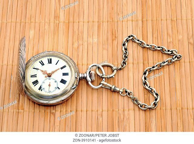 Alte Taschenuhr vor weißem Hintergrund / Old pocket watch in front of a white background