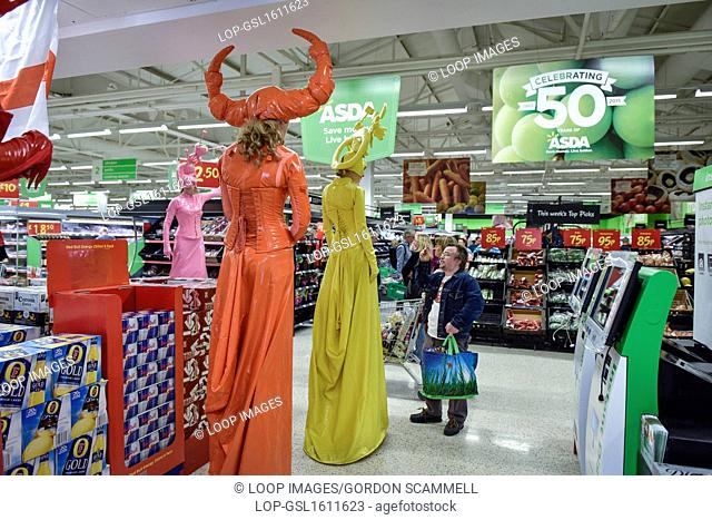 Jo Peacock and her cheeky cohorts dressed as candy coloured stiltwalkers wander around the interior of an ASDA store in South Woodham Ferrers