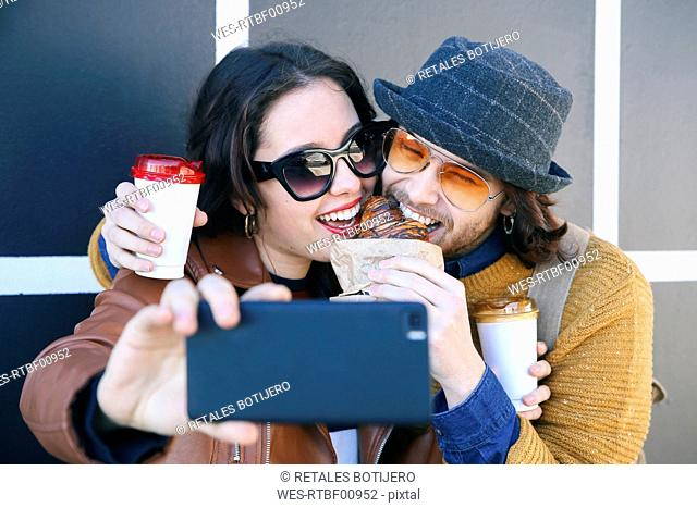 Young couple with croissant and coffee to go taking selfie with smartphone