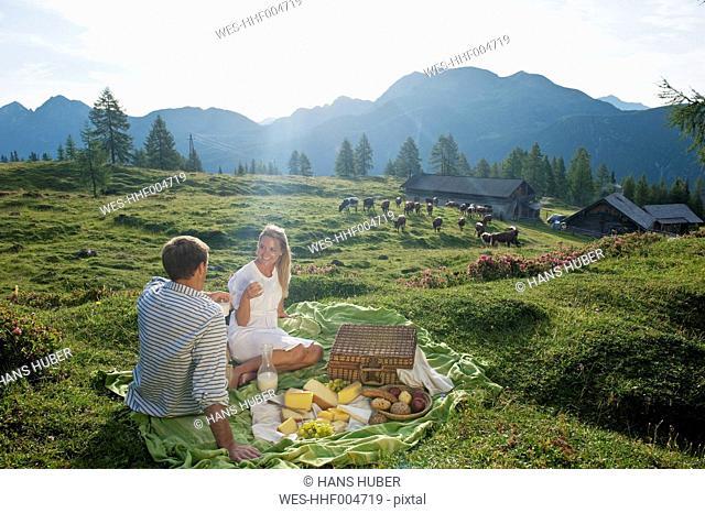 Austria, Salzburg State, Altenmarkt-Zauchensee, couple having a picnic on alpine meadow