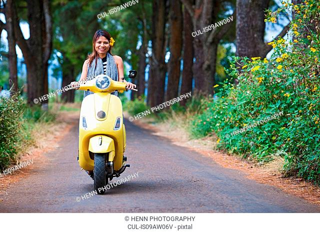 Mid adult woman on tree lined road on yellow scooter looking at camera smiling, Buon Ma Thuot, Dac Lak province, Vietnam