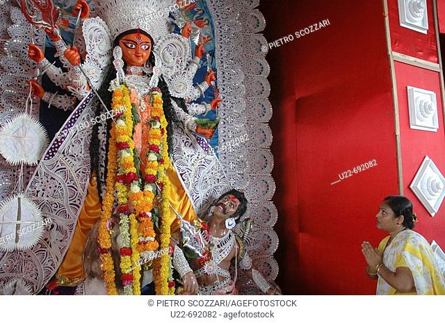 Panjim Goa, India: a woman praying to Durga's statue, during the Durga Puja hindu godness' feast, October