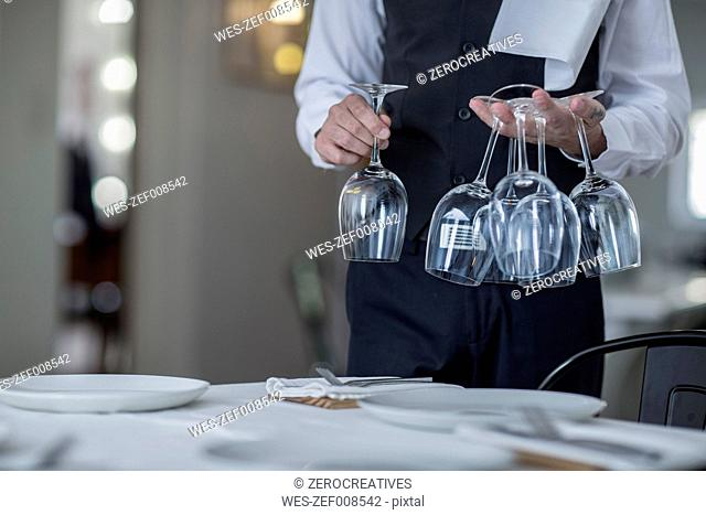 Waiter placing wine glasses on restaurant table