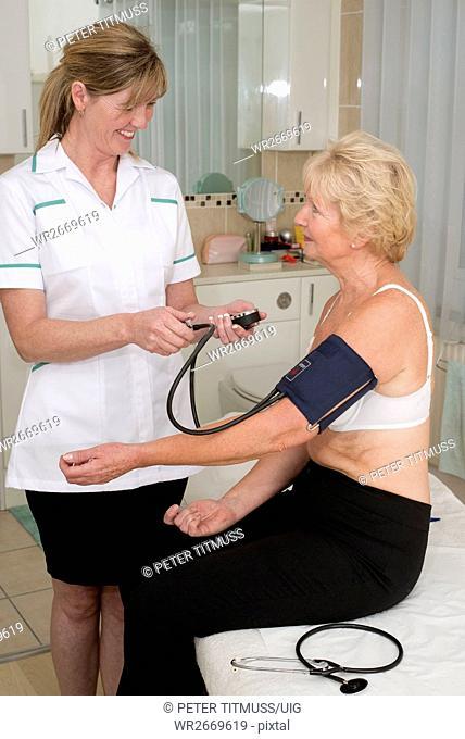 Nurse checking elderly woman's blood pressure