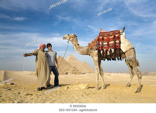 Two men in the desert with a camel with the Pyramids in the background