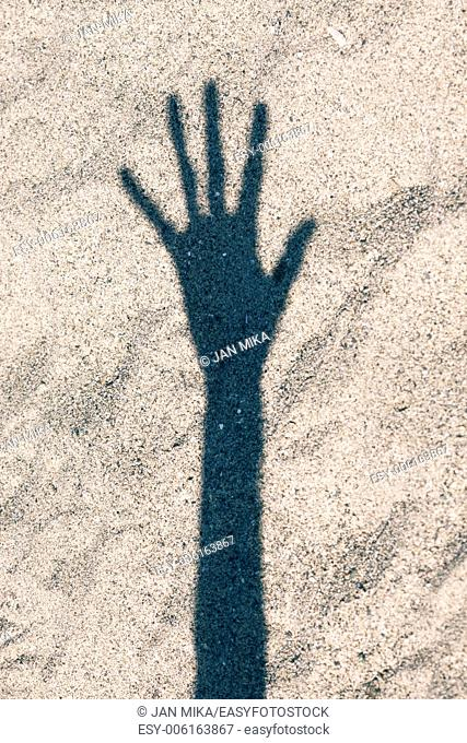 Shadow of hand over sand background