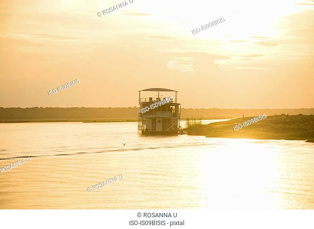 Boat on river at sunset, Chobe National Park, Botswana