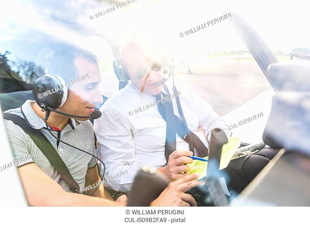 Pilot and co-pilot sitting in aircraft, talking through flight plan