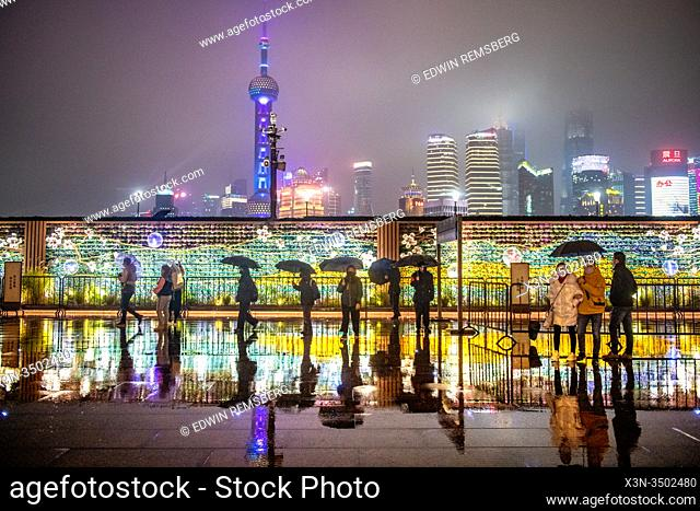 Decorative light wall backed by the brightly lit cityscape of Shanghai, China